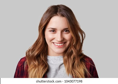 Headshot of beautiful smiling woman with broad smile, being in good mood as poses at camera, isolated over white background. Cheerful young female model poses alone in studio. Facial expressions