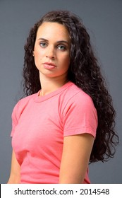 A headshot of a beautiful woman with brilliant green eyes and long, dark curly hair, in a salmon-colored shirt on a neutral grey background.