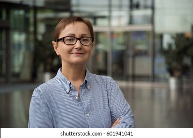 Headshot of business woman in the office background Portrait of older women wearing glasses and oxford long sleeve striped shirt. Caucasian brunette female with short haircut in her 40s 50s years old