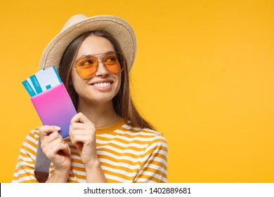 Headshot of Caucasian girl holding tickets for plane and passport ready for travelling, isolated on background