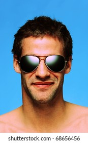 Headshot of a caucasian man in his late twenties with designer stubble wearing aviator sunglasses taken against a plain blue background, cross processed color effect.