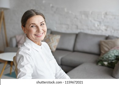 Headshot of charming senior retired woman with healthy skin with wrinkles and gathered grey hair relaxing in her modern living room, enjoying leisure time, looking at camera and smiling happily