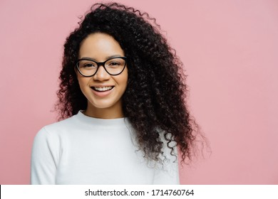 Headshot of charming young female with Afro hairstyle, smiles pleasantly at camera, feels very happy, wears transparent glasses and white jumper, isolated on rosy background. Amused ethnic female