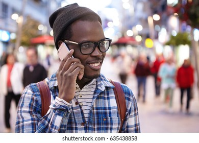 Headshot of cheerful modern young African tourist with backpack wearing hat and glasses having phone conversation while walking along crowded street during summer vacations in foreign country