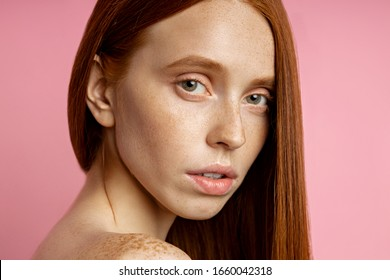 Headshot closeup portrait of serious caucasian female model with freckles, red hair, clean skin, bare shoulders, without makeup looking at camera with calm expression. Natural beauty concept.