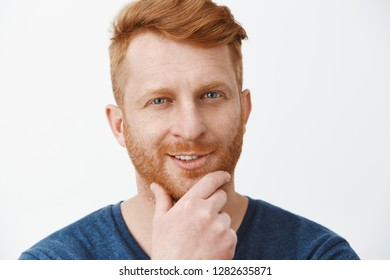 Headshot of creative and intrigued attractive redhead guy with bristle, rubbing beard and smirking, having great plan or idea gazing curiously at camera, standing interested over gray background
