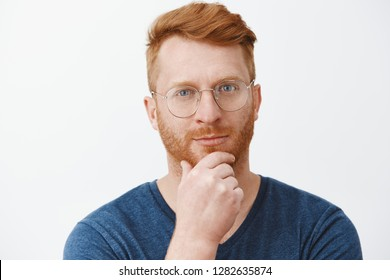 Headshot of creative and smart handsome redhead guy with bristle in glasses and blue t-shirt, rubbing beard on chin and gazing with smirk at camera, having great plan or idea over gray background