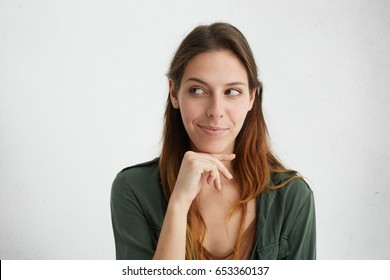 Headshot of cunning beautiful woman with straight dyed hair looking aside holding hand under chin indenting to realize tricky plan. Attractive female having sly expression while looking aside