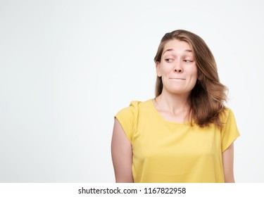 Headshot of cunning beautiful woman in yellow t-shirt looking aside indenting to realize tricky plan. Attractive female having sly expression while looking aside