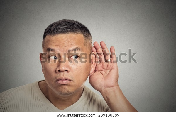 Headshot curious middle ged man listening to conversation news eavesdropping privacy concept isolated on grey wall background with copy space. Human face expression, reaction, emotion, life perception