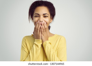Headshot of cute timid attractive young  female laughing from bottom of her heart, covering open mouth with hands and closing eyes. Human positive emotions and feelings.