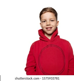 Headshot of cute toothy smiling little boy in trendy red sweatshirt. Portrait of male child wearing warm hooded sweater on white copy space. Kids fashion and outfit. Clothing collection for children