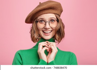 Headshot of delightful smiling clever woman with innocent expression, keeps hand together, has intriguing and happy look as recieves unexpected surprise or present from boyfriend. Emotions concept