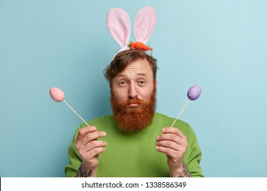 Headshot of displeased young Caucasian man with trendy hairstyle, red beard and mustache, sad to celebrate Easter alone, holds colored eggs on wooden stickers, prepares festive basket for church