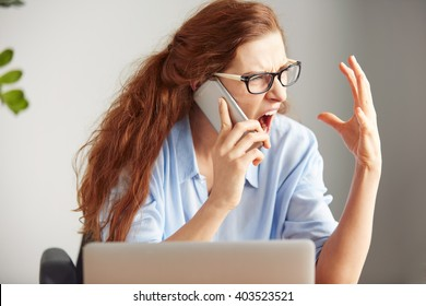 Headshot of a female boss shouting with anger on cell phone while sitting at desk in office. Portrait of an angry businesswoman screaming on mobile phone. Negative human emotions, facial expressions