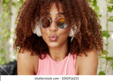 Headshot of funny beautiful female makes grimace, keeps lips rounded, wears trendy shades, has curly black hair, enjoys favourite song, has fun in coffee shop.