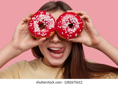 Headshot of funny young European woman covers eyes with two glazed doughnuts, licks lips with tongue, has dark hair, wants to eat sweet dish, isolated over pink background. Junkfood concept.