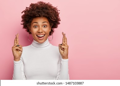 Headshot of glad smiling curly woman crosses fingers with positive expression, believes in good luck and success, looks hopefully straightly at camera, isolated over pink wall with blank space aside