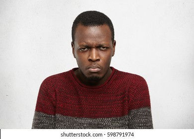 Headshot of grumpy unhappy young dark-skinned male dressed casually frowning and looking at camera with grimace, feeling angry or offended after having not been invited to party by his friends