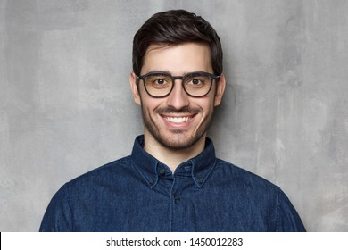 Headshot of guy wearing spectacles looking at camera with smile, isolated on background