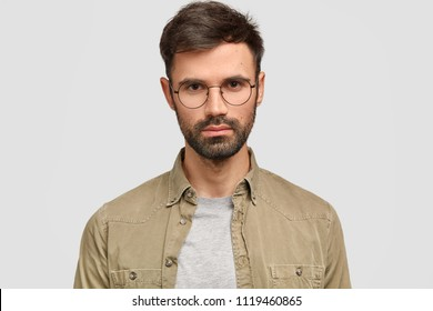 Headshot of handsome bearded serious young male freelancer with appealing appearance, looks directly at camera, dressed in fashionable shirt, works distantly, isolated over white background.