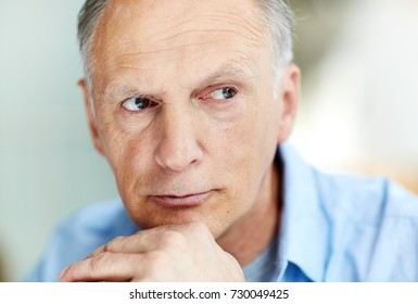 Headshot of handsome senior man wearing blue shirt looking away pensively, blurred background