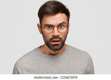 Headshot of handsome unshaven male reacts on something with displeased look, has surprised expression, stares at camera, dressed in casual clothes, isolated over white background. Emotions concept
