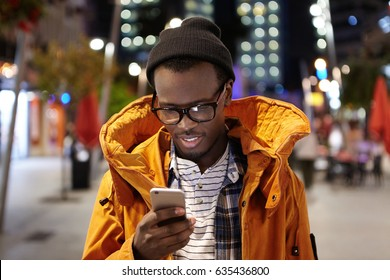 Headshot of handsome young Afro American student having walk around night city, holding mobile phone, using urban wifi, browsing pictures on social media. Modern technology and communication