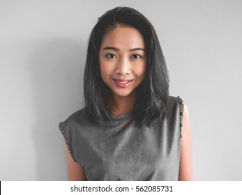 Headshot of happy Asian woman in grey dress.
