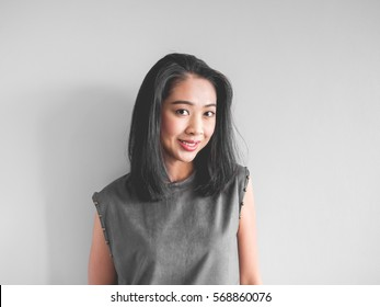 add2e6a8c3d41 Headshot of happy Asian woman in grey dress.