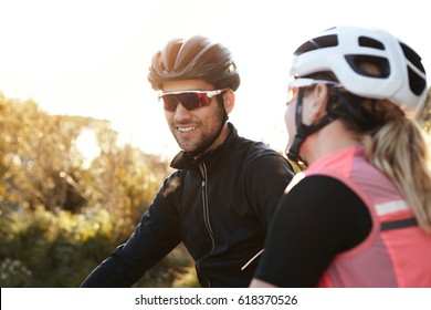 Headshot of happy and carefree European couple on bicycles, wearing helmets and special sunglasses, selective focus on cheerful man. Male and female feeling joy while riding bikes and sharing stories