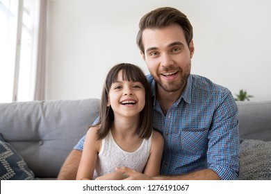 Headshot of happy cute kid daughter and friendly smiling father looking on webcam talking at camera make online video call, child with dad record vlog together, daddy and little daughter portrait