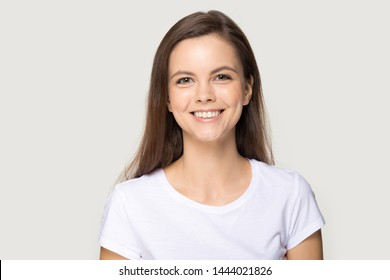 Headshot of happy millennial woman smiling looking at camera. Cheerful female portrait at studio isolated on grey background. Young brunette standing having good mood, beautiful smile. People emotions