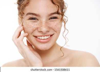 Headshot happy tender redhead girl freckles smiling broadly white teeth standing naked gently touching cheek taking care body showering, applying skincare cosmetics treatment, daily hygiene procedure