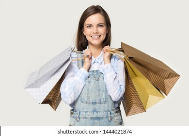 Headshot of happy young woman holding paper packages in hands. Studio portrait of millennial female carrying shopping bags smiling looking at camera isolated on gray background. Buy, purchase concept