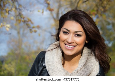 Head-shot of a hispanic woman outdoors during a fall day