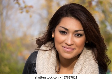 Head-shot of a hispanic woman outdoors during an autumn day
