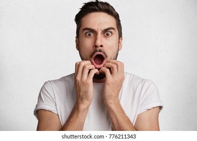 Headshot of horrified bearded male stares at camera, keeps jaw dropped out, being terrified as watches horror film, sees viloent murder, wears casual t shirt, frowns face in dissatisfaction.