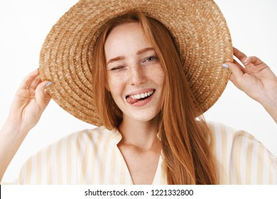 Headshot of joyful attractive redhead female in straw hat with freckles winking happily and sticking out tongue enjoying sunny warm summer day on vacation walking on beach smiling broadly