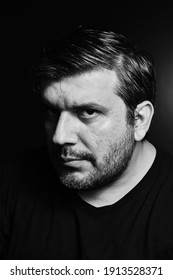 Headshot of a man staring intensely at the camera in black and white