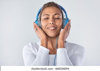 Headshot of mature woman enjoying listening to music with large headphones in studio