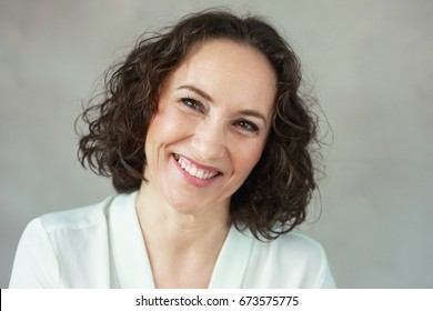 headshot of mature woman laughing posing next to color background