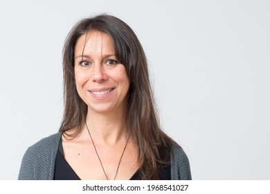 Headshot of a mediterranean woman aged 30-40 with a friendly big smile and white background