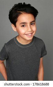 headshot of mixed race boy smiling on gray background