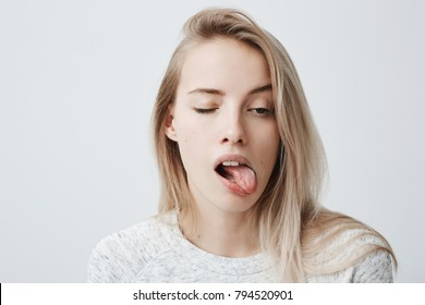 Headshot of naughty girl of European appearance with blonde long hair sticking out tongue, closing one eye, trying to tease someone, looking immature and offensive, grimacing and making faces.
