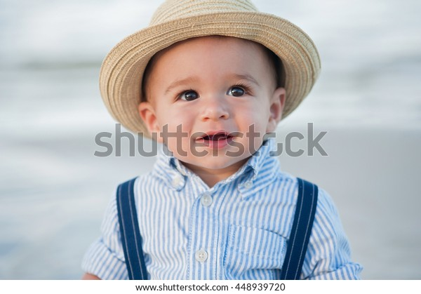 A headshot of a one year old baby boy wearing a straw fedora hat.