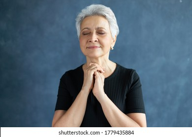 Headshot of peaceful beautiful mature female with short gray hair posing isolated having hopeful facial expression, keeping eyes closed, holding hands clasped in prayer, hoping for the best