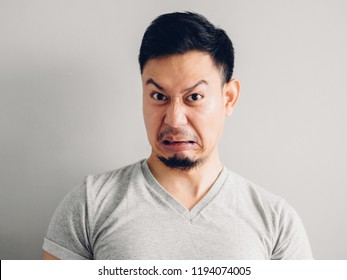 Headshot photo of Asian man with hate and disgusting face. on grey background.