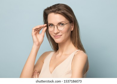 Headshot portrait of beautiful Caucasian woman isolated on blue studio background wear glasses look at camera, millennial female in spectacles posing advertising optician, sight correction treatment
