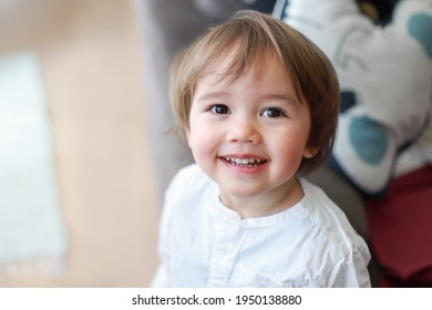 Headshot portrait of cute baby boy about 1-2 years old wearing white shirt with smiling face at home. Happy mixed race Asian-German child relaxing with copy space for text.
